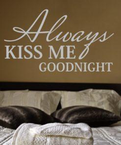 Primer izgleda sive samolepilne stenske nalepke Always kiss me goodnight na kavni steni nad posteljo Nalepka je napis, ki se glasi: Always kiss me goodnight