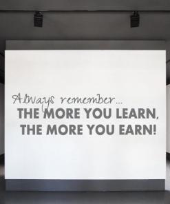 Primer izgleda grafitno sive stenske nalepke Always remember the more you learn na beli steni v galeriji. Nalepka je napis, ki se glasi: Always remember... the more you learn, the more you earn!