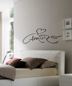 Nadomestno besedilo + besedilo v sliki Primer izgleda grafitno sive stenske nalepke Amore na krem steni nad posteljo v spalnici. Nalepka je napis, ki se glasi: Amore