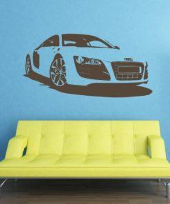 Primer izgleda črne samolepilne stenske nalepke Audi R8 na modri steni v dnevni sobi.