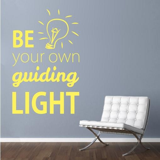 Primer izgleda rumene stenske nalepke Be your own light na sivi steni nad foteljem v dnevni sobi. Nalepka je napis, ki se glasi: Be your own guiding light.