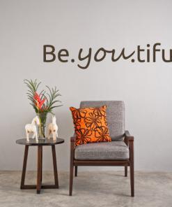 Primer izgleda čokoladno rjave stenske nalepke BeYouTiful na svetlo sivi steni nad počivalnikov v dnevni sobi. Nalepka je napis, ki se glasi: BeYouTiful.