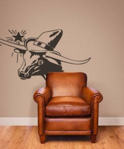 Primer izgleda čokoladno rjave samolepilne stenske nalepke Bik s klobukom na bež steni v dnevni sobi.
