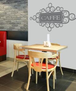 Primer izgleda grafitno sive stenske nalepke Caffe na beli steni v kavarni. Nalepka je napis, ki se glasi: Caffe.