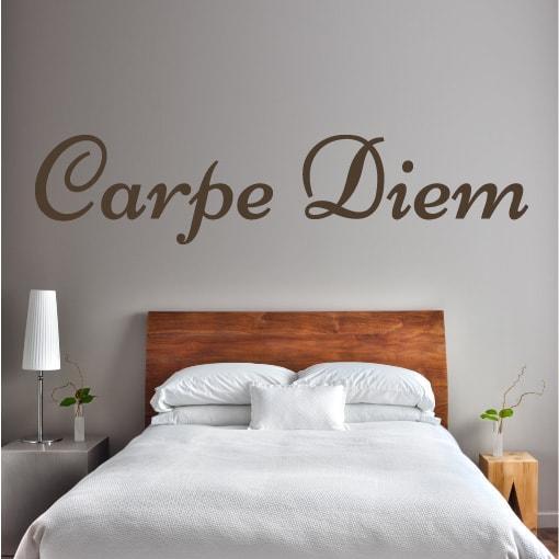 Nadomestno besedilo + besedilo v sliki Primer izgleda čokoladno rjave stenske nalepke Carpe Diem na svetlo sivi steni nad posteljo v spalnici. Nalepka je napis, ki se glasi: Carpe Diem.