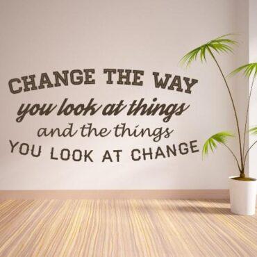 Primer izgleda čokoladne rjave stenske nalepke Change the way you look at things na beli steni. Nalepka je napis, ki se glasi: Change the way you look at things and the things you look at change.