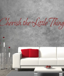 Primer izgleda rdeče samolepilne stenske nalepke Cherish the little things na sivi betonski steni v dnevni sobi. Nalepka je napis, ki se glasi: Cherish the little things.