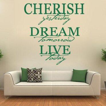 Primer izgleda zelene samolepilne stenske nalepke Cherish yesterday dream na krem steni nad sedežno v dnevni sobi. Nalepka je napis, ki se glasi: Cherish yesterday, dream tomorrow, live today.