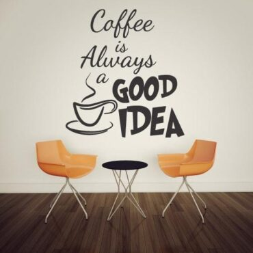 Primer izgleda temno sive samolepilne stenske nalepke Coffee is Always na beli steni v restavraciji. Nalepka je napis, ki se glasi: Coffee is Always a good idea.