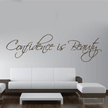 Primer izgleda čokoladno rjave samolepilne stenske nalepke Confidence is Beauty na beli steni. Nalepka je napis, ki se glasi: Confidence is Beauty.