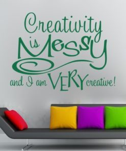 Primer izgleda zelene samolepilne stenske nalepke Confidence is Messy na svetlo sivi steni nad moderno sedežno. Nalepka je napis, ki se glasi: Creativity is Messy and I am very creative!
