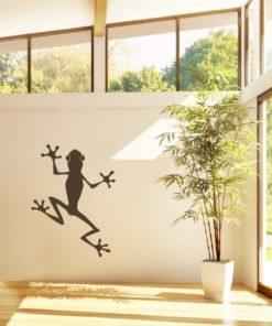 Primer izgleda črne samolepilne stenske nalepke Črna žaba na bež steni v dnevni sobi.