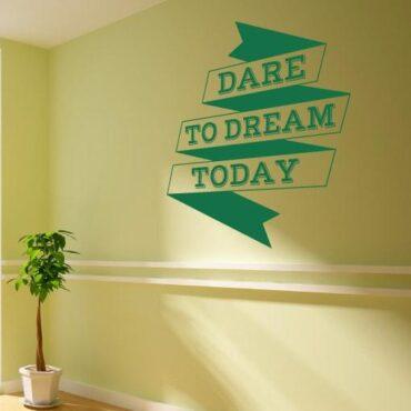 Primer izgleda zelene samolepilne stenske nalepke Dare to dream today na svetlo rumeni steni. Nalepka je napis, ki se glasi: Dare to dream today.