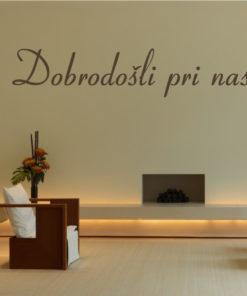 Primer izgleda čokoladno rjave samolepilne stenske nalepke Dobrodošli pri nas 2 na kapucino steni. Nalepka je napis, ki se glasi: Dobrodošli pri nas.