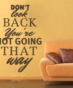 Primer izgleda čokoladno rjave samolepilne stenske nalepke Don't look back na oranžni steni ob zofi. Nalepka je napis, ki se glasi: Don't look back you're not going that way.