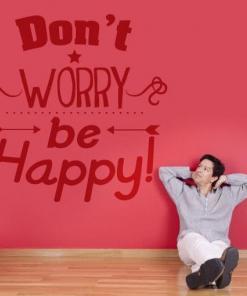 Primer izgleda temno rdeče samolepilne stenske nalepke Don't worry be happy na rdeči steni. Nalepka je napis, ki se glasi: Don't worry be happy.