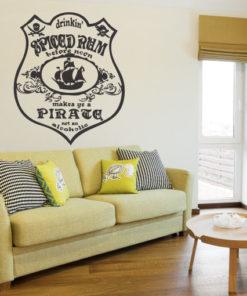 Primer izgleda grafitno sive samolepilne stenske nalepke Drinking spiced rum na bež steni nad zofo. Nalepka je napis, ki se glasi: Drinking spiced rum before noon. Make by a Pirate not an alcoholic.