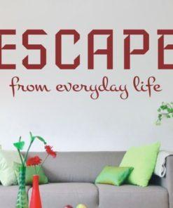 Primer izgleda temno rdeče samolepilne stenske nalepke Escape na beli steni v dnevni sobi nad zofo. Nalepka je napis, ki se glasi: Escape from everyday life.