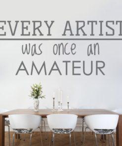 Primer izgleda sive samolepilne stenske nalepke Every artist na beli steni v jedilnici nad mizo. Nalepka je citat Ralph Waldo Emerson, ki se glasi: Every artist was once an amateur.