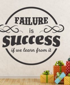 Primer izgleda črne samolepilne stenske nalepke Failure is success if we learn from it na bež steni. Nalepka je napis, ki se glasi: Failure is success if we learn from it.