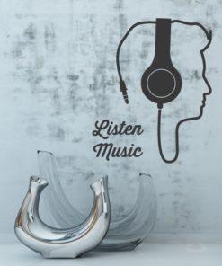 Primer izgleda črne samolepilne stenske nalepke Glava iz slušalk na sivi steni.