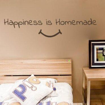 Primer izgleda čokoladno rjave samolepilne stenske nalepke Happiness is Homemade na bež steni v spalnici. Nalepka je napis, ki se glasi: Happiness is Homemade.