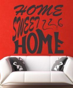 Primer izgleda grafitno sive samolepilne stenske nalepke Home sweet home poševno na rdeči steni. Nalepka je napis, ki se glasi: Home sweet home.