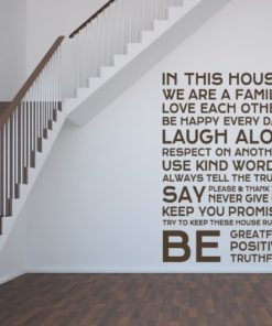 Primer izgleda čokoladno rjave samolepilne stenske nalepke House rules 3 na beli steni na hodniku. Nalepka je napis, ki se glasi: In this house: We are a family, Love each other, Be happy every day, LAUGH ALOT, Respect on another, Use kind words, Always tell the truth, Say okease and thank you, Never give up, Keep you promise, Try to keep these house rules, BE greatful, positive and truthful!