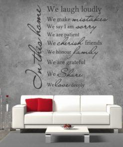 Primer izgleda črne samolepilne stenske nalepke House rules 4 na sivi steni v dnevni sobi nad sedežno. Nalepka je napis, ki se glasi: In this home: We laugh loudly We make mistakes. We say I am sorry. We are patient. We cherish friends. We are grateful. We share. We love deeply.