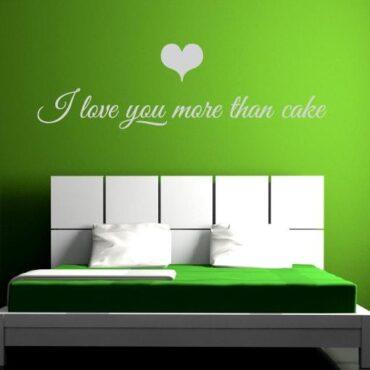 Primer izgleda bele samolepilne stenske nalepke I love you more then cake na zeleni steni v spalnici. Nalepka je napis, ki se glasi: I love you more then cake.
