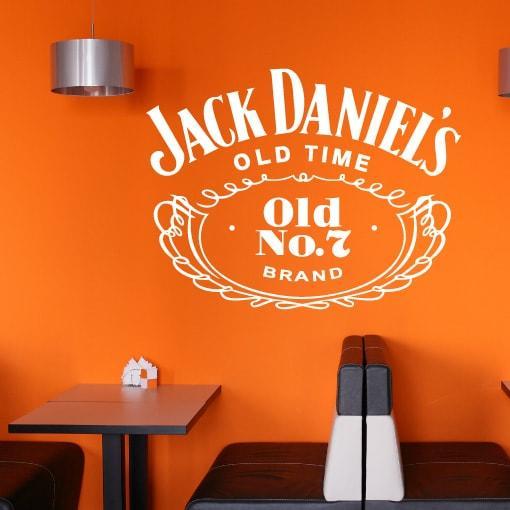 Primer izgleda bele samolepilne stenske nalepke Jack Daniels na oranžni steni v jedilnici. Nalepka je napis, ki se glasi: Jack Daniels OLD TIME Old No. 7 Brand