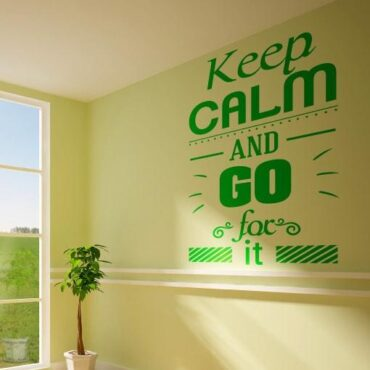 Primer izgleda zelene samolepilne stenske nalepke Keep calm and go for it na rumeno zeleni steni. Nalepka je napis, ki se glasi: Keep calm and go for it.