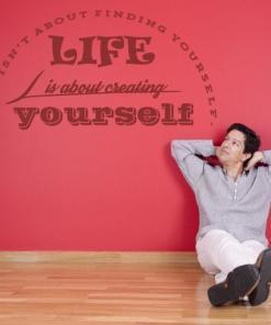 Primer izgleda temno rdeče samolepilne stenske nalepke Life is about na rdeči steni. Nalepka je napis, ki se glasi: Life isn't about finding yourself. LIFE is about creating yourself.