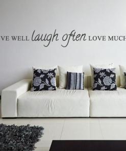 Primer izgleda črne samolepilne stenske nalepke Live well Laugh often Love much na beli steni v dnevni sobi. Nalepka je napis, ki se glasi: Live well, Laugh often, Love much.