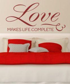 Primer izgleda temno rdeče samolepilne stenske nalepke Love na bež steni v spalnici. Nalepka je napis, ki se glasi: Love makes life complete.