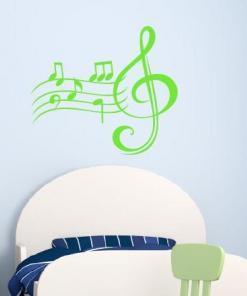 Primer izgleda zelene samolepilne stenske nalepke Note in violinski ključ na beli steni.
