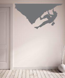 Primer izgleda grafitno sive samolepilne stenske nalepke Plezalka na bež steni v dnevni sobi.