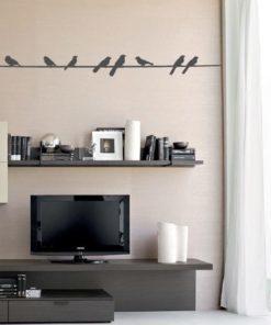 Primer izgleda črne stenska nalepka Ptički na kablu na beli steni v dnevni sobi.