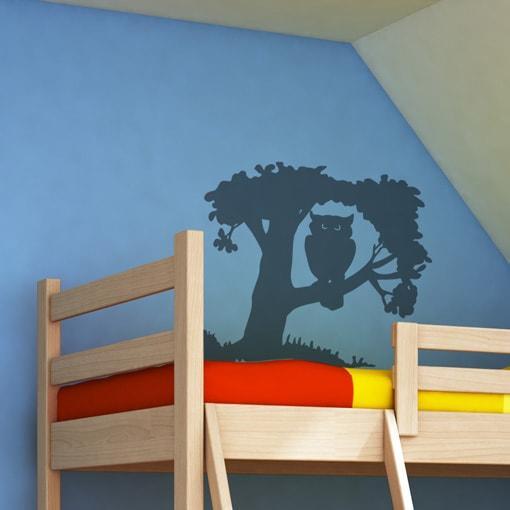 Primer izgleda črne stenska nalepka Sova na drevesu na modri steni v otroški sobi.