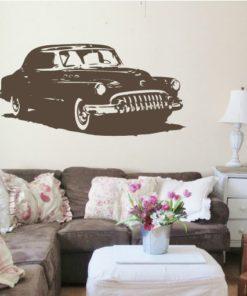 Primer izgleda čokoladno rjave samolepilne stenske nalepke Vintage avto na bež steni v dnevni sobi.