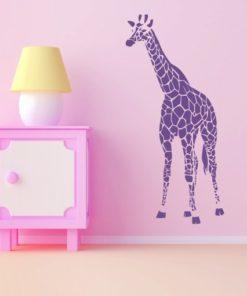 Primer izgleda vijolične stenska nalepka Žirafa na roza steni v otroški sobi.