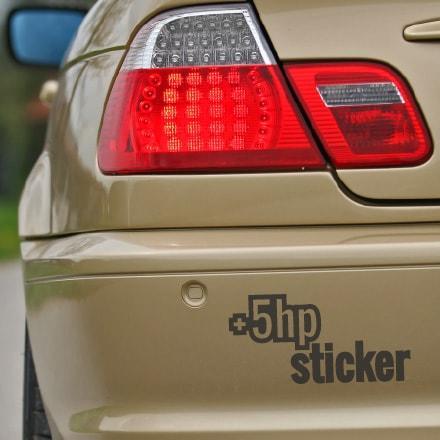 Primer izgleda črne samolepilne avto nalepke +5hp sticker na rjavim avtu.