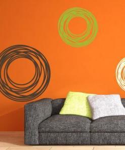 Primer izgleda rjave, zelene in bele samolepilne stenske nalepke Art krog na oranžni steni v študentski sobi nad sedežno.