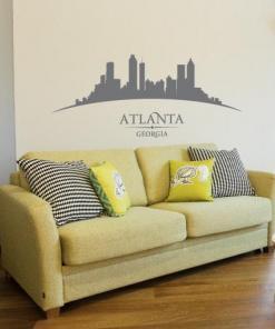 Primer izgleda grafitno sive samolepilne stenske nalepke Atlanta ukrivljen na bež steni nad zofo v dnevni sobi.