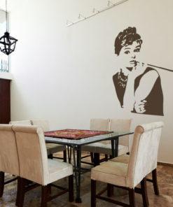 Primer izgleda čokoladno rjave samolepilne stenske nalepke Audrey Hepburn na bež steni v jedilnici.