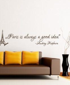 Primer izgleda čokoladno rjave samolepilne stenske nalepke Audrey Hepburn Citat - Paris is always a good idea na bež steni v jedilnici. Nalepka je citat Audrey Hepburn, ki se glasi: Paris is always a good idea.