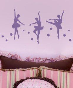 Primer izgleda vijolične samolepilne stenske nalepke Balerine na roza steni nad posteljo v otroški sobi.