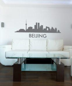 Primer izgleda grafitno sive samolepilne stenske nalepke Beijing na beli steni v dnevni sobi.