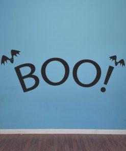 Primer izgleda črne samolepilne stenske nalepke Boo! na modri steni v otroški sobi.