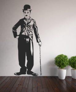 Primer izgleda črne samolepilne stenske nalepke Charlie Chaplin na beli steni v dnevni sobi.